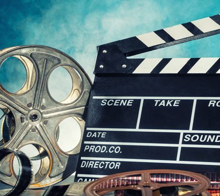 A Movie Clapboard And Movie Reel On Blue Background.