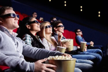 A Set of People Enjoying A 3D Movie In Theatre.