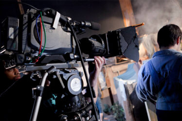 A Commercial Movie Director Standing Infront of The Professional Camera.